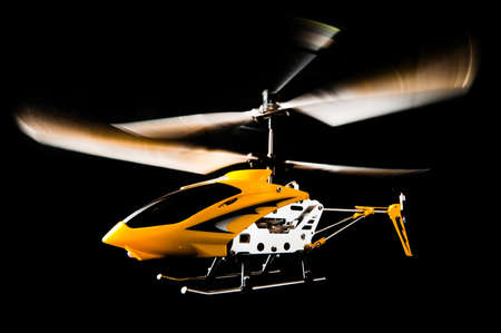 Radio controlled helicopter isolated on black, working, with blurred airscrews