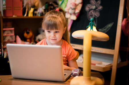 In small room young girl looking in her laptop and smiling