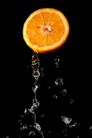 Fresh and bright orange part and waterdrops flying photo