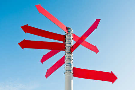 Multi-directional empty sign with many red arrows on post