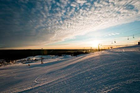 Ski resort at sunrise with few tracks and trails