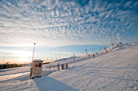 Ski slope at sunrise with few tracks and trails photo