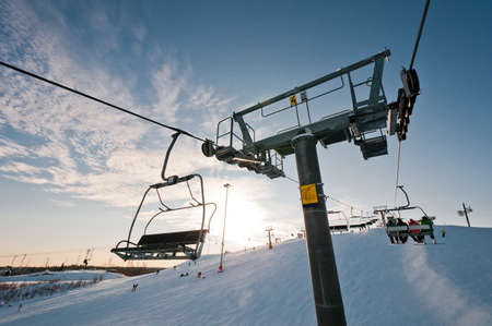 Top part of ski-lift support and few chairs on wires placed on ski resort Stock Photo