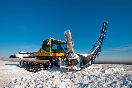 Snowcat for making half pipes, standing on top of the mountain photo