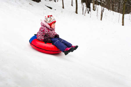 Child on inflatable sleds riding down from slope photo