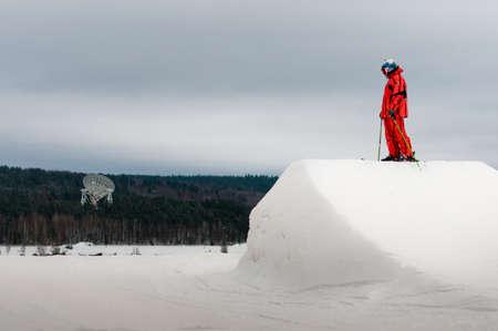 springplank: Skier in oranje suite staat op springplank piek tijdens de training