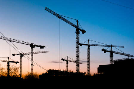 construction machinery: Many cranes silhouettes on clear and blue sky