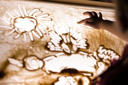 Child paint an illustration with sand on light table by finger