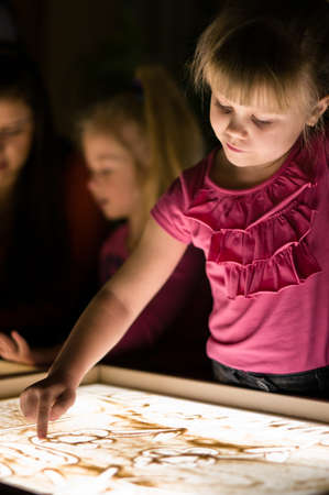 sand art: Girl paint with sand on table by her finger in classroom with friends