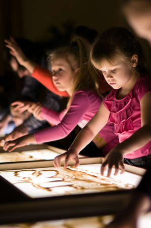 Girl paint with sand on table by her fingers in classroom with friends