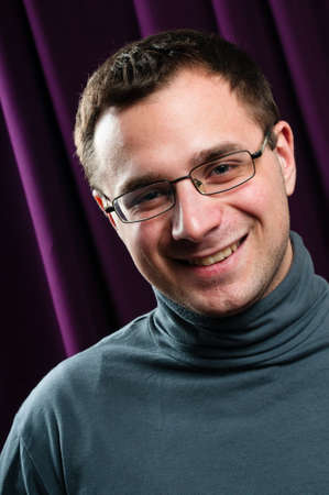 Smiling man with glasses portrait with purple curtain on background Stock Photo