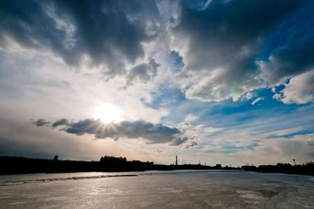 Cloudscape over the city silhouette and frozen river at winter Stock Photo