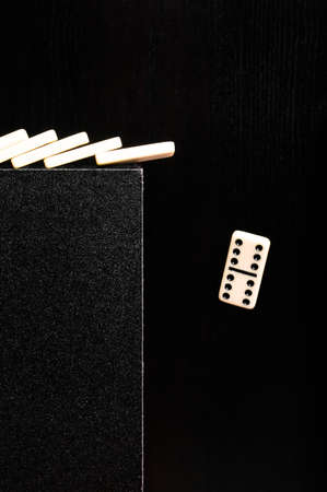 Domino dropping from the edge of black and textured box Stock Photo