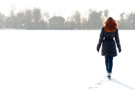winter field: Pretty red haired girl walking on frozen lake and making footpath