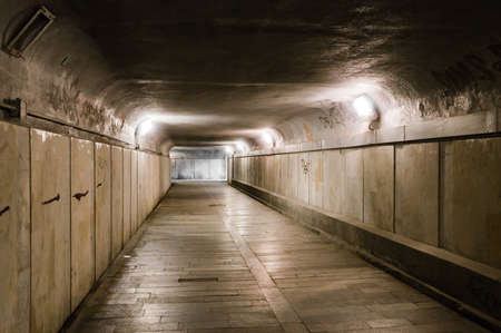 Old abandoned underground tunnel partly illuminated with lamps Stock Photo - 13164138