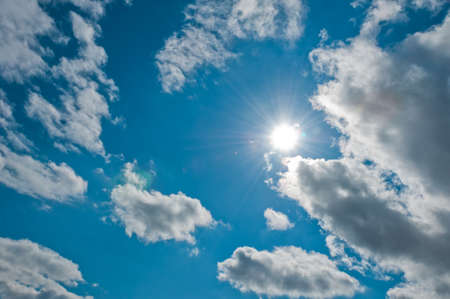 Blue sky with beautiful cloudscape and sun with sunbeams photo