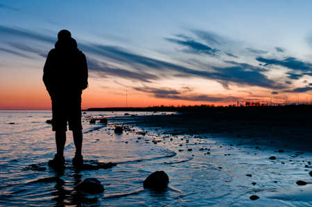 cirrus: Traveler looking on sunset, standing in water near beach Stock Photo