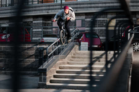 Biker doing double peg grind down the hand rail over the stairs photo