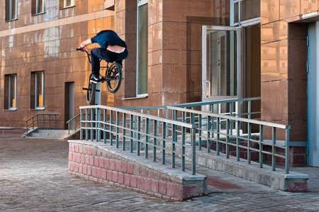 Biker doing high rail hop trick on bmx, back view