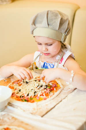 finally: Little girl finally adding last ingredient - cheese - in pizza