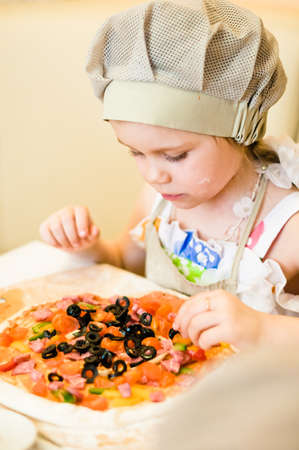 making fun: Little girl adding ingredients, vegetables and meat, in pizza