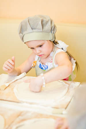 Little girl continue cooking pizza and working with dough photo