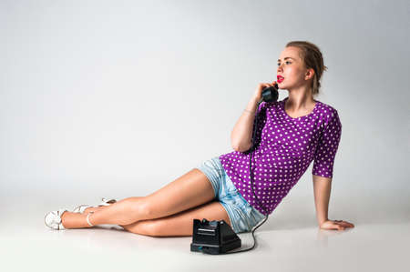 Pin up girl talking by vintage phone, studio shot photo