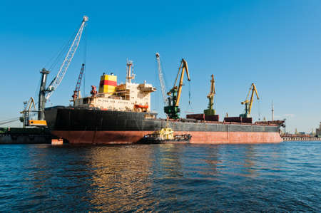 Big ship unloading in shipyard at day time with clear sky Stock Photo - 13697884