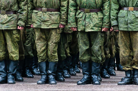 Soldiers in camouflage stand in formation legs only view photo