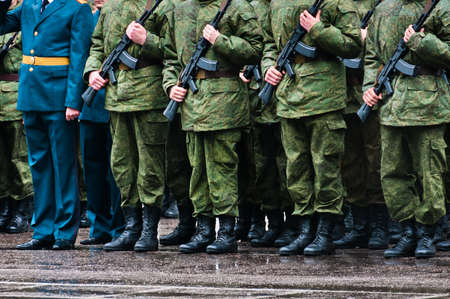 Soldiers in camouflage stand in formation with officer in blue clothing Stock Photo