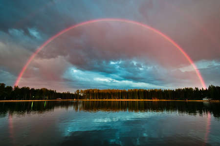 rainbow scene: Full beautiful rainbow arc over the lake with still water