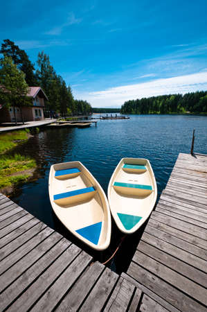Two empty boats floating near wooden pier in camp