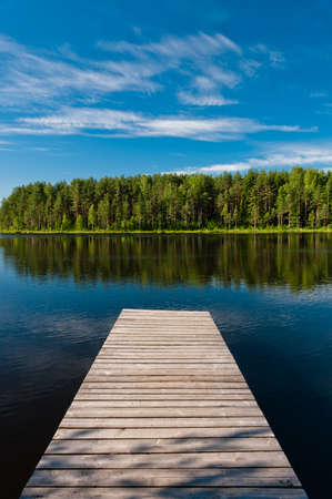 Muelle de madera en el lago escena simétrica, vista vertical con el bosque Foto de archivo