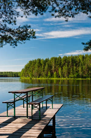Wooden pier on lake with benches, beautiful nature view