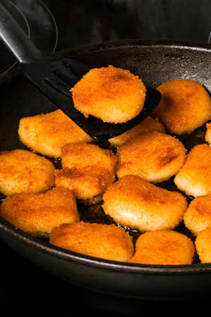 Fried nuggets in pan with one nugget on spatula