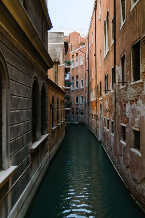 Venice narrow waterway with old houses on both sides Stock Photo