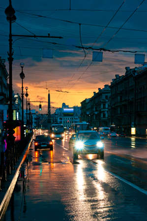 Cars on wet road at night in the center of the city photo