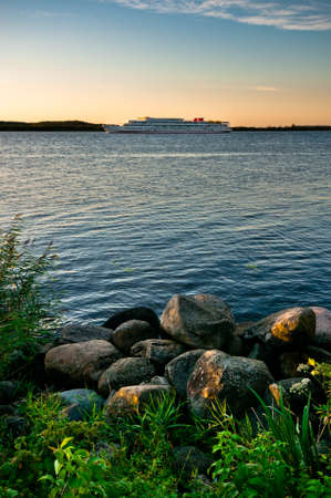 Landscape with rocky coastline and remote ship at sunset