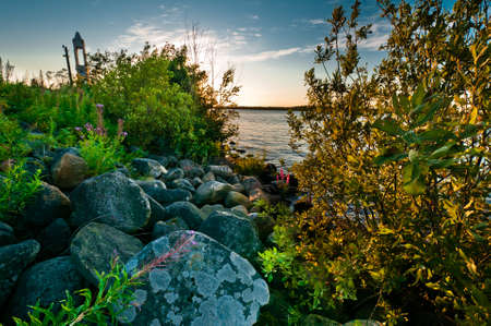 Landscape with many stones, lake, clouds and colorful plants