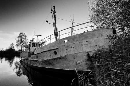 Old, rusty and damaged ship on still water in black and white