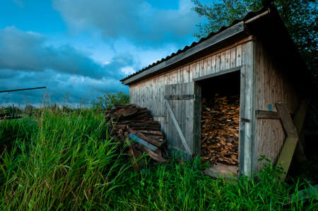 Old and hand made barn for firewood with grass and beautiful cloudscape Stock Photo