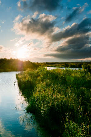 River and land with grass scene with beautiful cloudscape on background Stock Photo