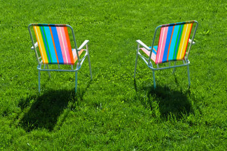 Two colorful chairs standing on grass at back yard