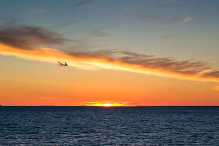 Beautiful sunset with cloud like a line and rippled sea Stock Photo