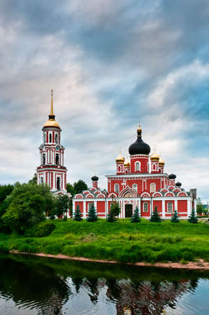 Red church on coast of the lake in Russian village