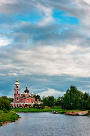 Red church with beautiful cloudscape on coast of the lake photo