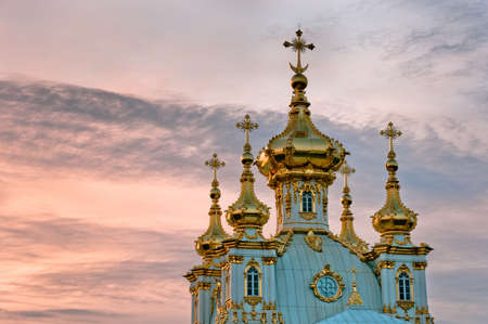 Golden domes of Petergof palace in park at twilight Stock Photo
