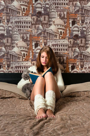 Girl sitting in bedroom and reading with city art on background is like imagination Stock Photo