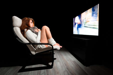 big screen tv: Girl sitting in front of large display in dark room with black background
