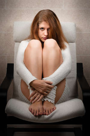 Girl sitting on chair in room and hugs her legs